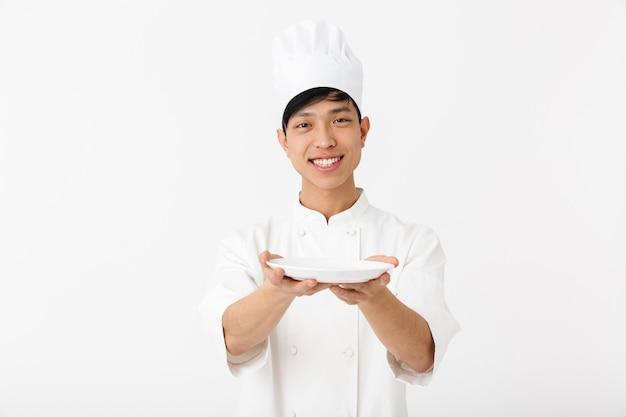 Homem chefe positivo asiático com uniforme branco de cozinheiro, sorrindo para a câmera enquanto segura um prato isolado na parede branca