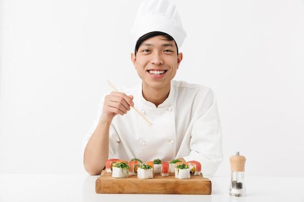 Homem chefe tipo asiático, com uniforme de cozinheiro branco, comendo sushi com pauzinhos isolados na parede branca