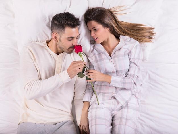 Homem, cheirando, rosa, cama, com, mulher