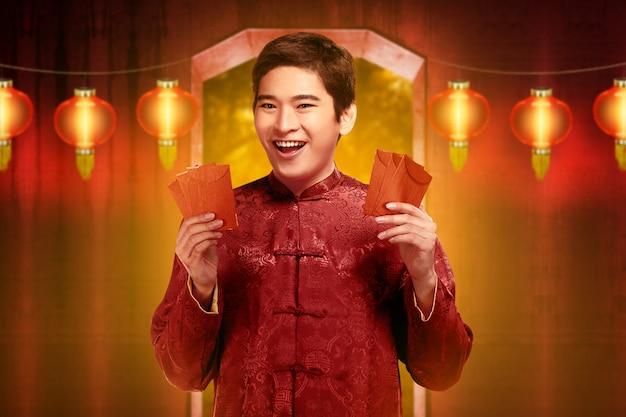 Homem chinês bonito em roupas tradicionais segurando angpao