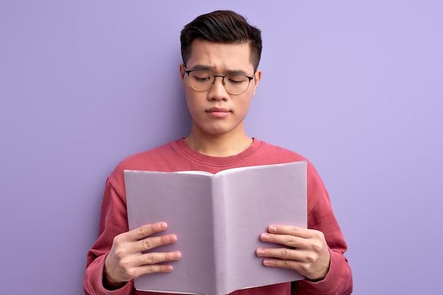 Homem chinês bonito lendo livro isolado no estúdio, cara asiático de óculos estudando