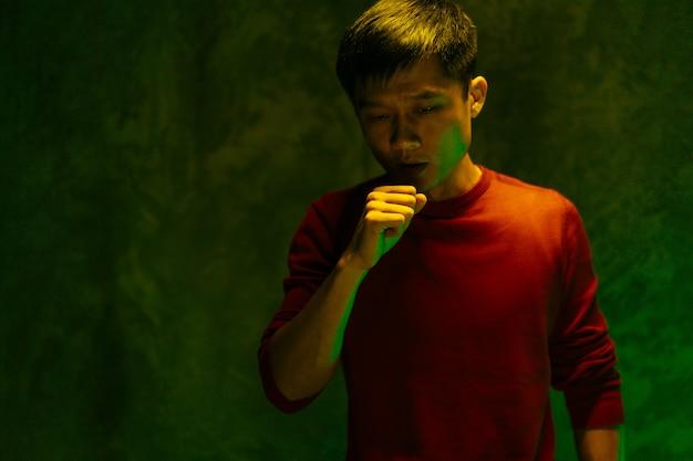 Homem chinês cobrindo a boca e tossindo. conceito de surto de coronavírus