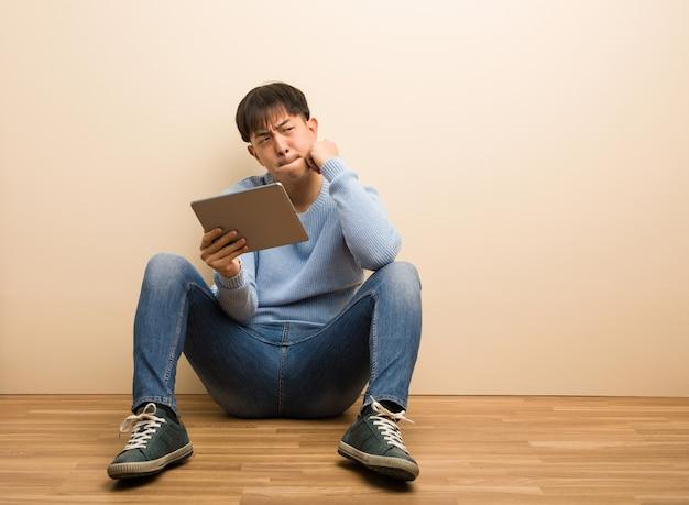 Homem chinês novo que senta-se usando sua tabuleta que pensa sobre uma ideia