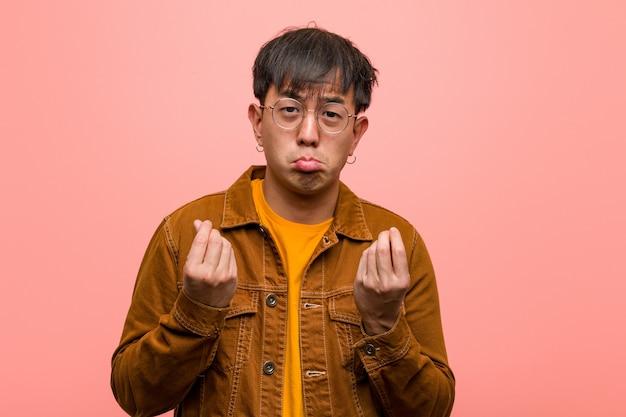 Homem chinês novo que veste um revestimento que faz um gesto da necessidade
