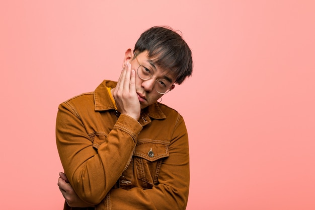 Homem chinês novo vestindo uma jaqueta cansado e com muito sono