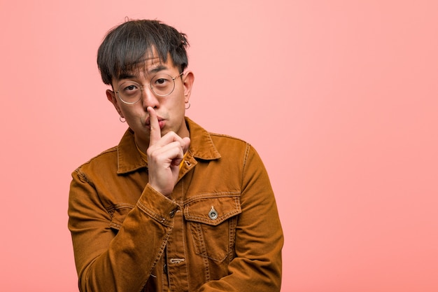 Homem chinês novo vestindo uma jaqueta, mantendo um segredo ou pedindo silêncio