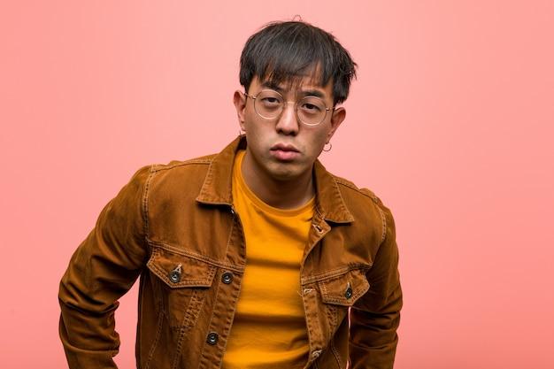 Homem chinês novo vestindo uma jaqueta repreendendo alguém muito zangado