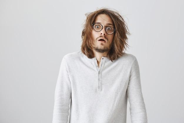 Homem chocado assustado com cabelo bagunçado parece assustado