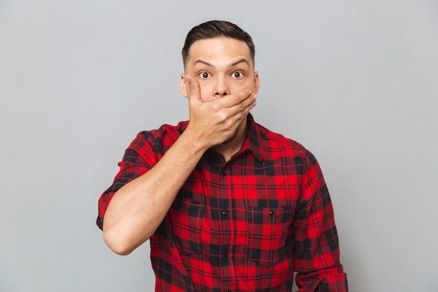 Homem chocado, cobrindo a boca