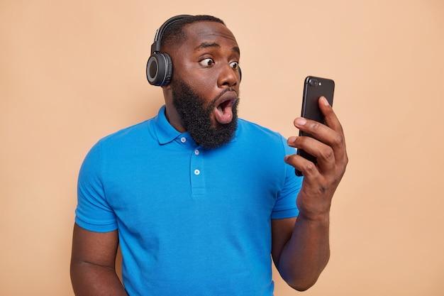 Homem chocado com barba espessa encara com olhar inacreditável a tela do smartphone e usa fones de ouvido sem fio nas orelhas, vestido com uma camiseta azul casual isolada sobre uma parede bege