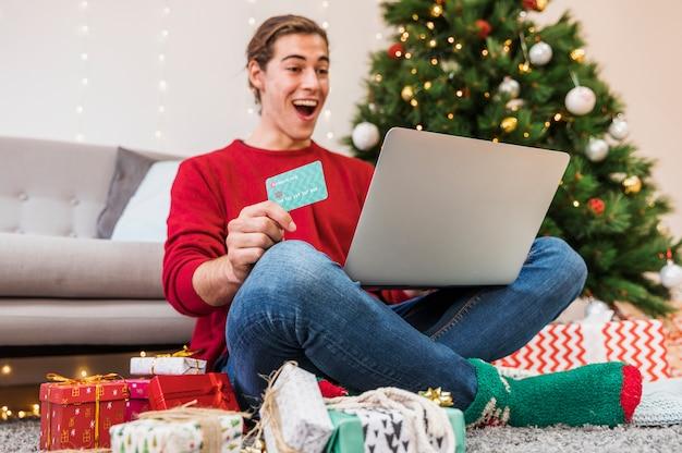 Homem chocado com cartão de crédito e laptop