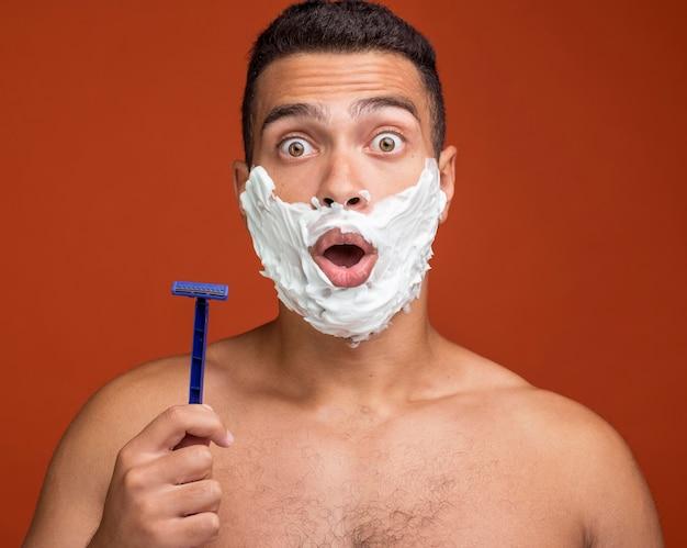 Homem chocado com espuma de barbear no rosto segurando uma navalha