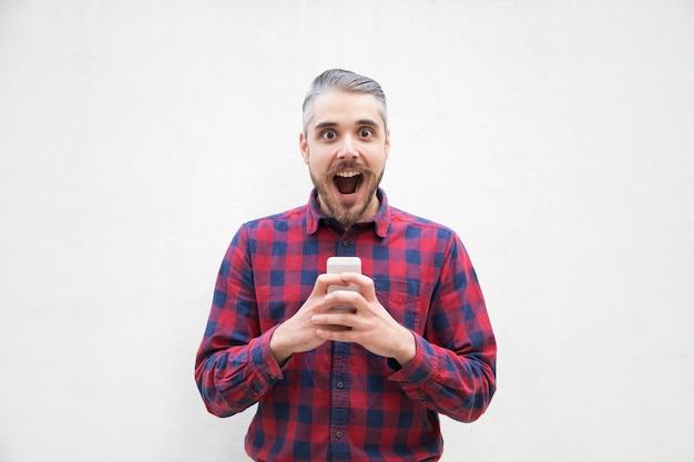 Homem chocado com telefone móvel olhando