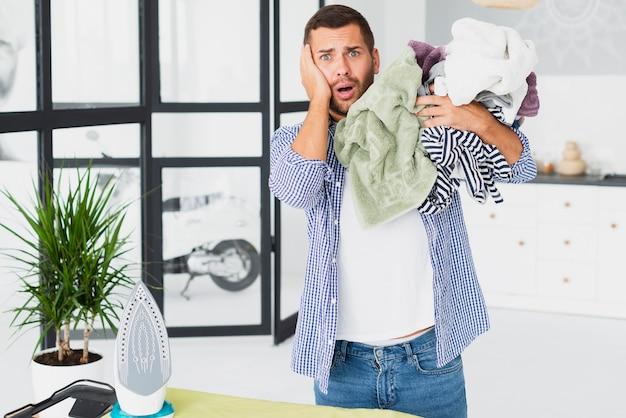 Homem chocado com todas as roupas a serem passadas