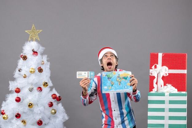 Homem chocado de frente com chapéu de papai noel com mola em espiral segurando mapa-múndi e bilhete de viagem