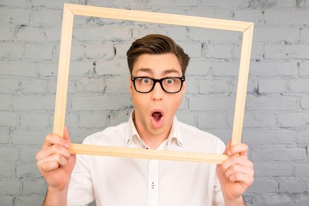 Homem chocado de óculos fazendo uma careta com a boca aberta dentro da fraime
