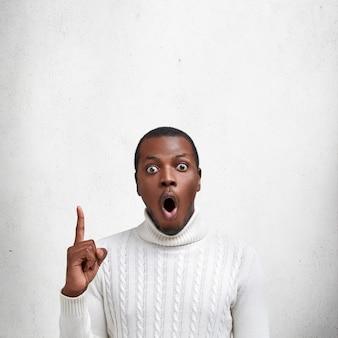 Homem chocado de pele escura, olhos esbugalhados e expressão de surpresa, usa suéter branco, indica com o dedo da frente para cima