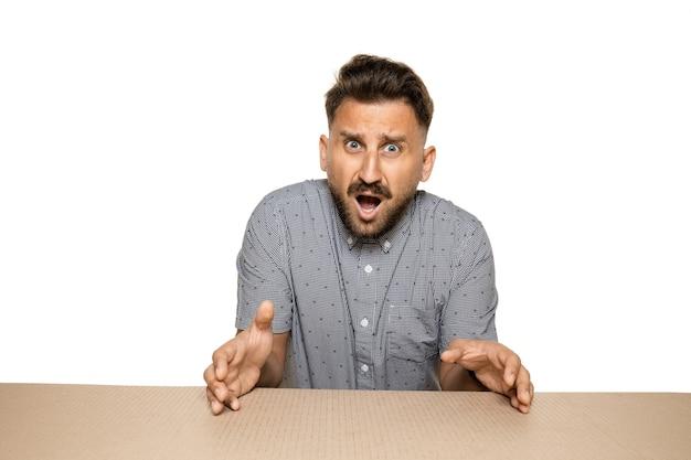 Homem chocado e chateado abrindo o maior pacote postal