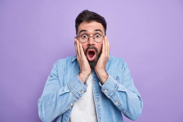 Homem chocado e fascinado mantém as mãos no rosto, boca bem aberta verifica algo terrível olha através dos óculos e usa camisa jeans