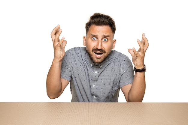 Homem chocado e surpreso abrindo o maior pacote postal