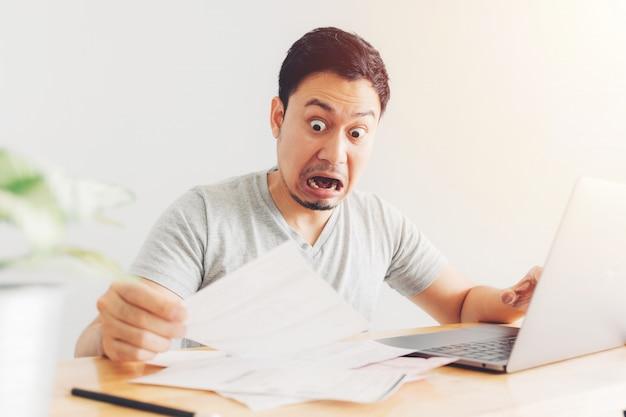 Homem chocado e surpreso tem os problemas com faturamento e dívidas.
