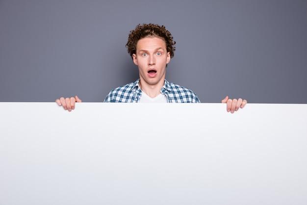 Homem chocado elegante em uma camisa xadrez casual segurando uma placa promocional branca