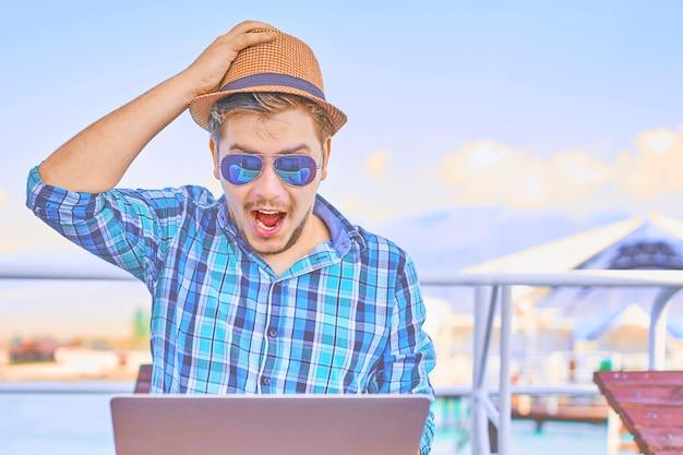 Homem chocado na camisa e chapéu em dia de sol no cais à beira-mar, surpreso por algo