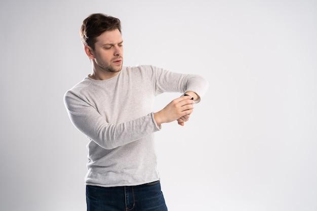 Homem chocado olhando no relógio de pulso, sobre fundo branco.