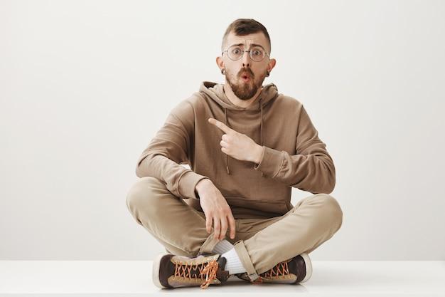 Homem chocado sentado no chão, apontando o dedo para a esquerda e parecendo preocupado