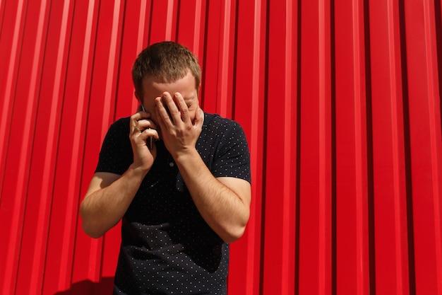 Homem chocado usando o celular sobre fundo vermelho, com espaço livre. jovem de pé sobre o fundo da parede vermelha com telefone móvel