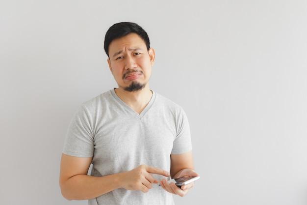 Homem chora e triste com o que mostra no smartphone.