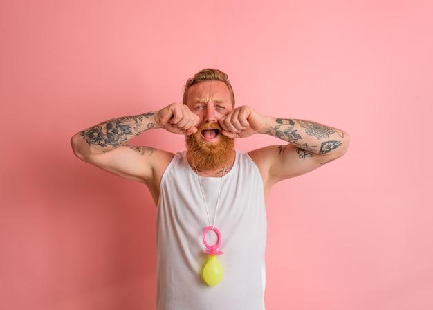 Homem chorando com barba e tatuagens age como um pequeno recém-nascido