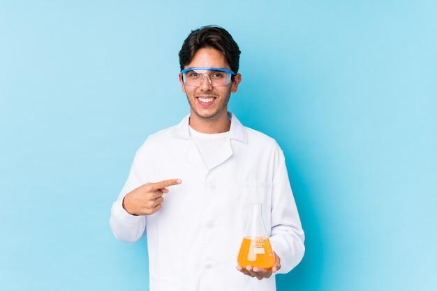 Homem cientific jovem isolado pessoa apontando à mão para um espaço de cópia de camisa, orgulhoso e confiante