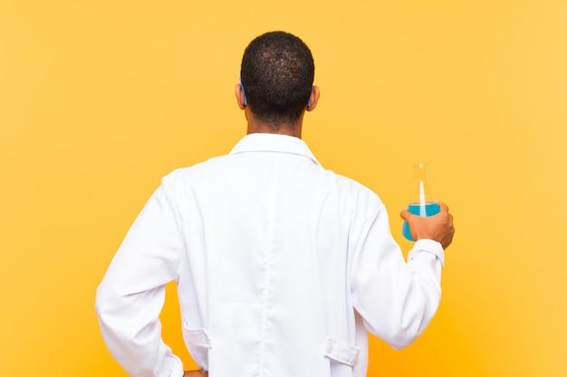 Homem científico segurando um balão de laboratório na posição traseira
