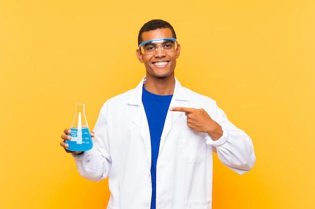 Homem científico segurando um balão de laboratório sobre fundo isolado e apontando-o