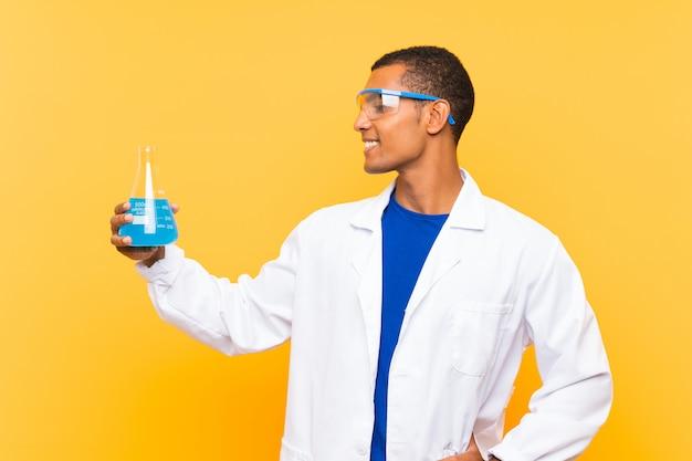 Homem científico segurando um balão de laboratório sobre parede isolada com expressão feliz