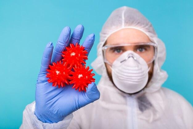 Homem cientista ou médico vestido com traje de proteção pessoal segura modelo de coronavírus