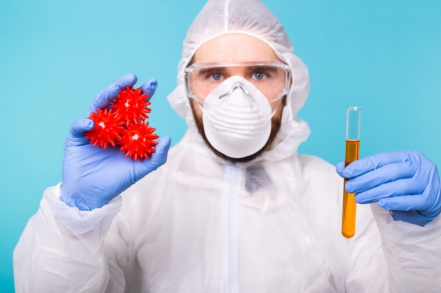 Homem cientista vestido com pano de proteção pessoal segura um modelo de coronavírus e tubo de ensaio