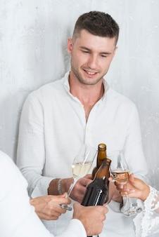 Homem, clanging, garrafa cerveja, com, amigos