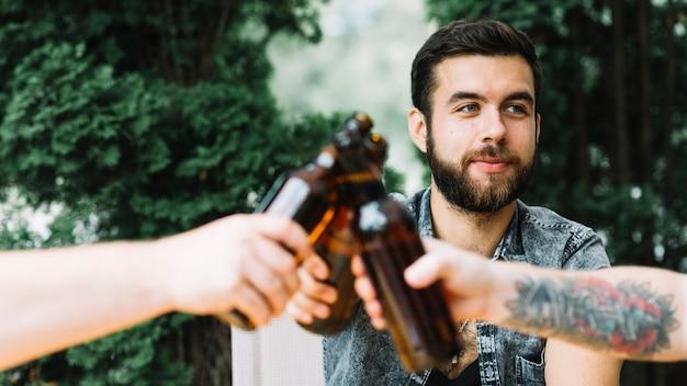 Homem, clinking, garrafas cerveja, com, seu, amigos