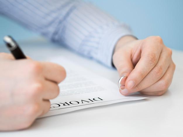 Homem close-up com aliança e contrato de divórcio