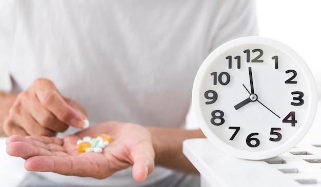 Homem close-up com pílulas e relógio