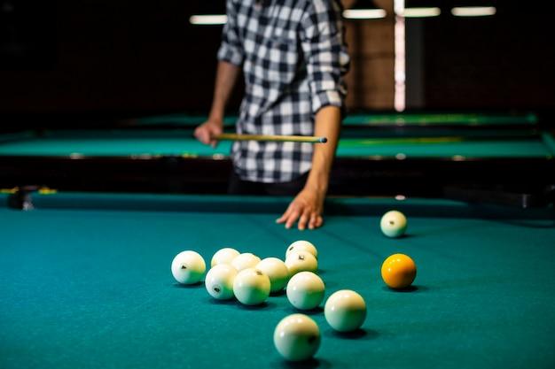 Homem close-up com taco de bilhar e bolas brancas