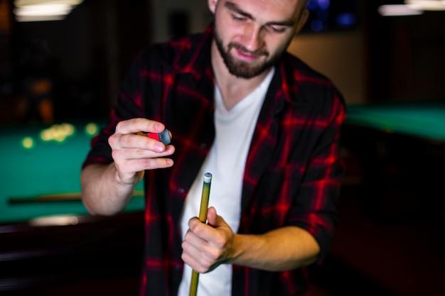 Homem close-up com taco de bilhar e giz