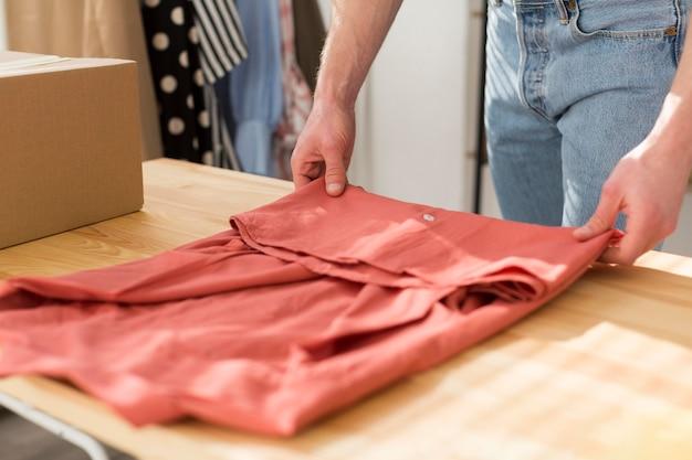 Homem close-up, dobrar roupa