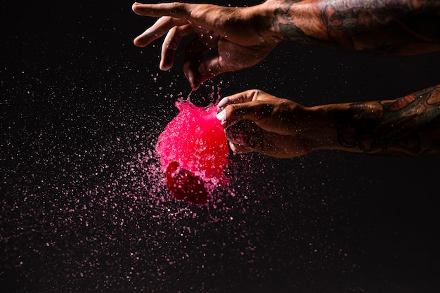 Homem close-up, estourando um balão com tinta vermelha