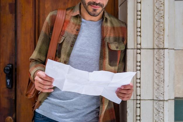 Homem close-up, lendo o mapa para orientação