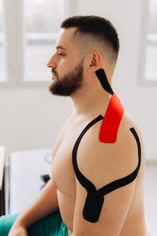 Homem close-up, levantando os braços. esportista com fita de kinesio no ombro e braço após lesão de treino no ginásio.