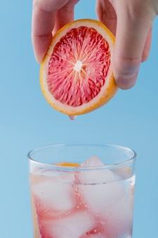 Homem close-up, segurando a fatia de laranja vermelha