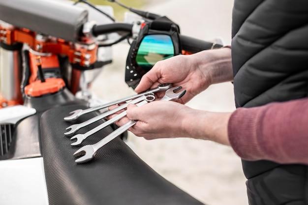 Homem close-up segurando chaves inglesas mecânicas